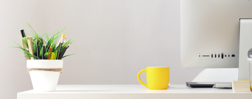 Desktop with computer monitor, yellow mug and small white pot